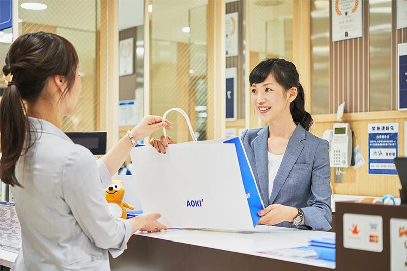 アオキ(AOKI)の店員が商品をお客様に渡している写真
