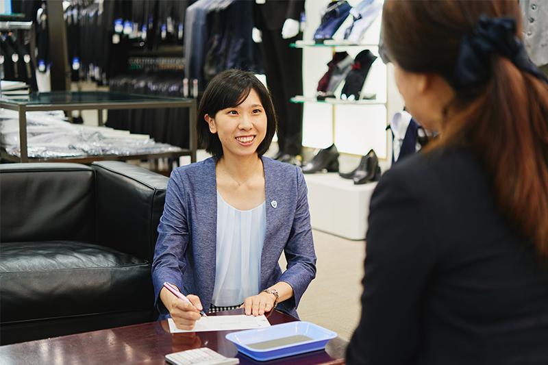 アオキ(AOKI)の女性店員が商品のお会計の準備をしている写真