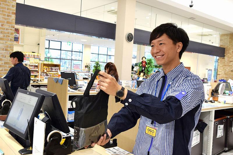 男性店員さんがレジから商品を渡している画像