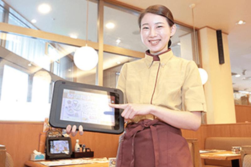 女性店員さんがメニューのタッチパネルを操作している画像