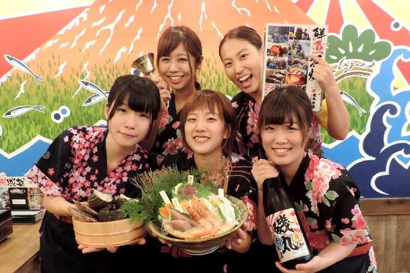 磯丸水産の女性店員たちが料理やお酒を持って集まっている画像