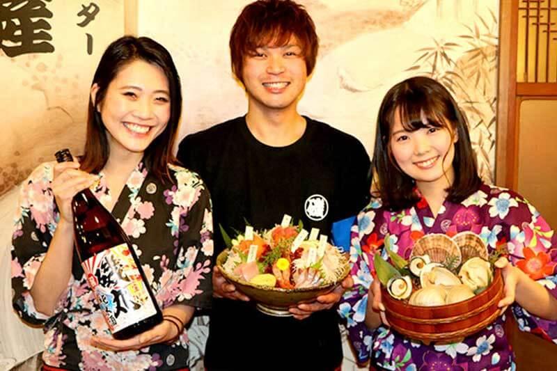 磯丸水産の男性店員と女性店員が料理を持っている画像