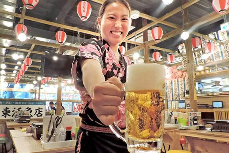 磯丸水産の女性店員がビールを提供している画像