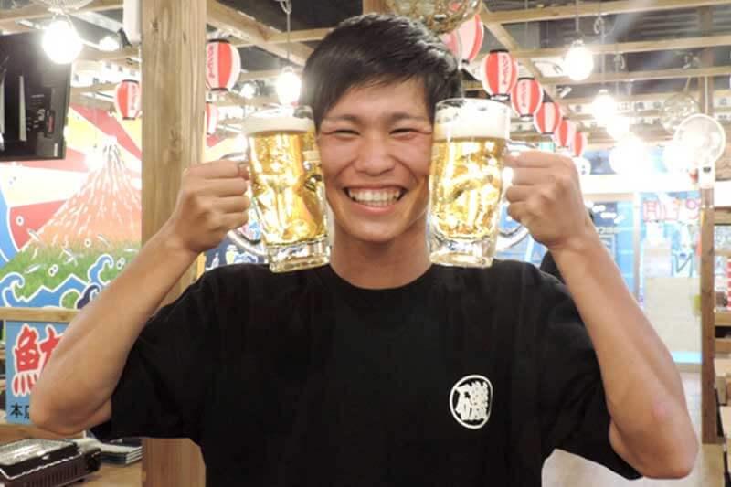 磯丸水産の男性店員がビールを二つ持っている画像