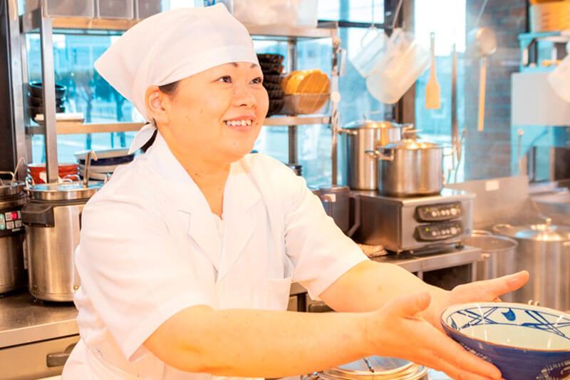 丸亀製麺の店員さんがうどんを渡している画像