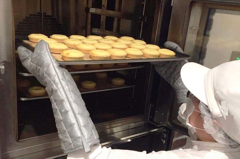 チーズケーキをオーブンに入れ焼こうとしている画像