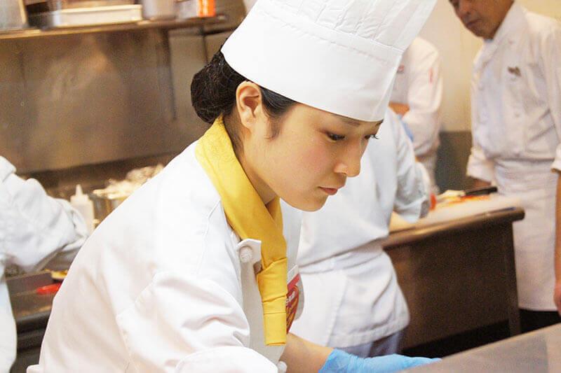 キッチンで調理をしている女性シェフの画像
