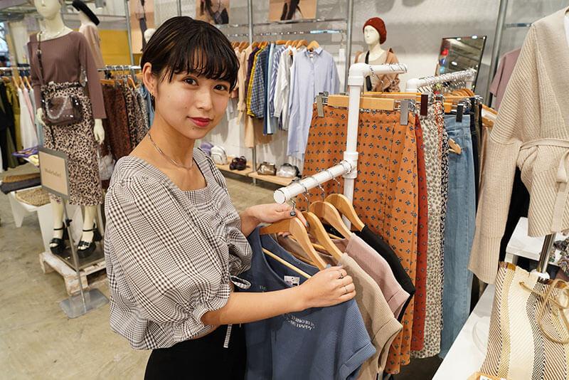 女性店員が服を陳列している画像