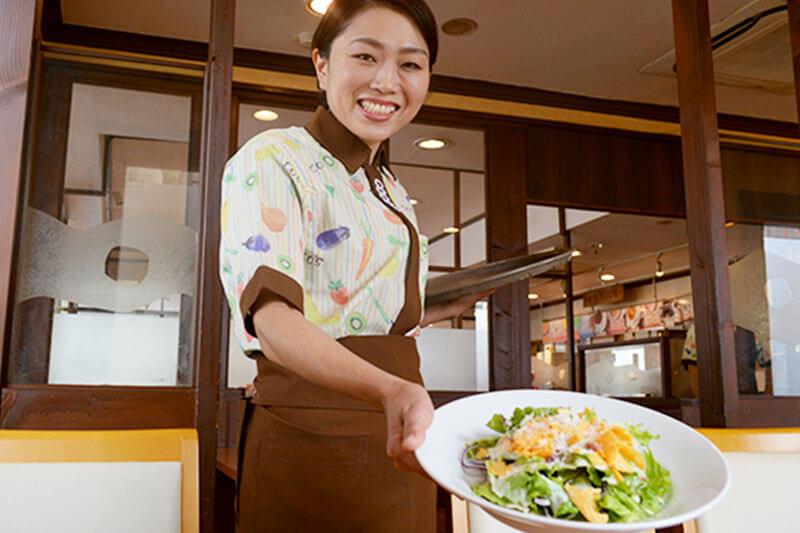 COCO'Sのホールスタッフが料理をサーブし接客をしている画像