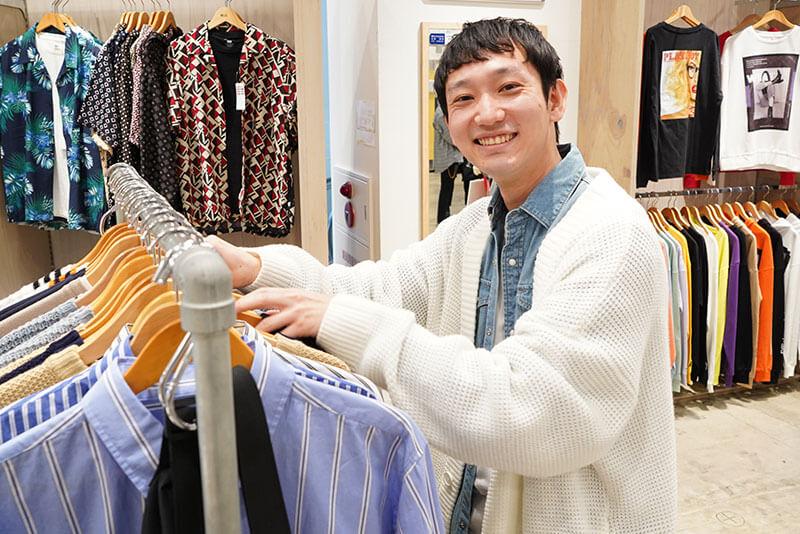 男性店員が服を整理している画像