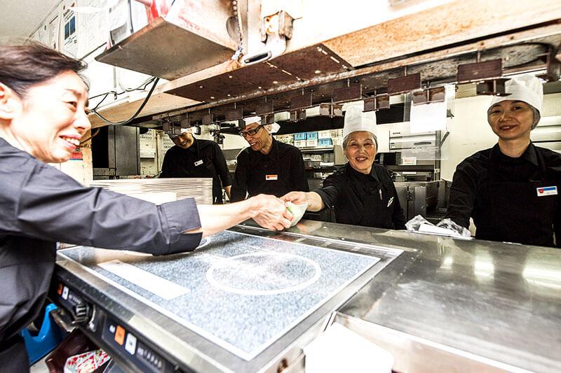 キッチンスタッフとホールスタッフで料理の受け渡しをしている画像