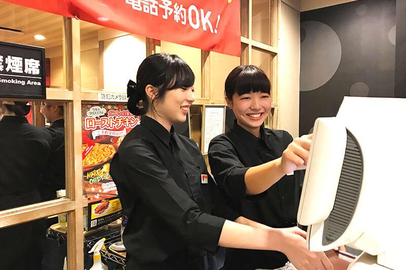 女性店員がレジで作業をしている画像