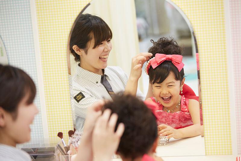 小さい子供のヘアメイクを直してあげている画像