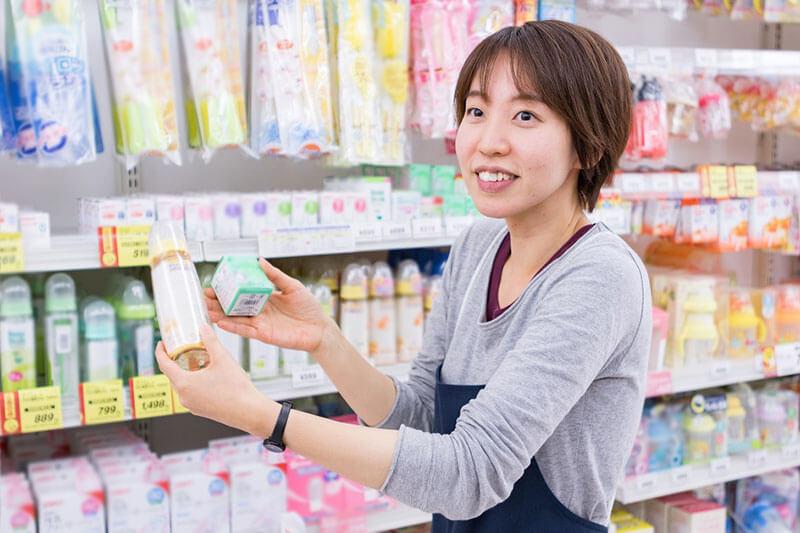 哺乳瓶等の商品をお客さんに見せている画像