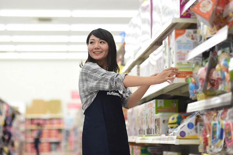 西松屋の店員さんがおもちゃの売っている棚を整理している画像