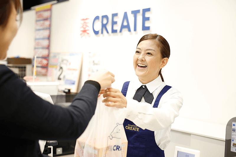 女性店員さんがレジで商品を渡している画像