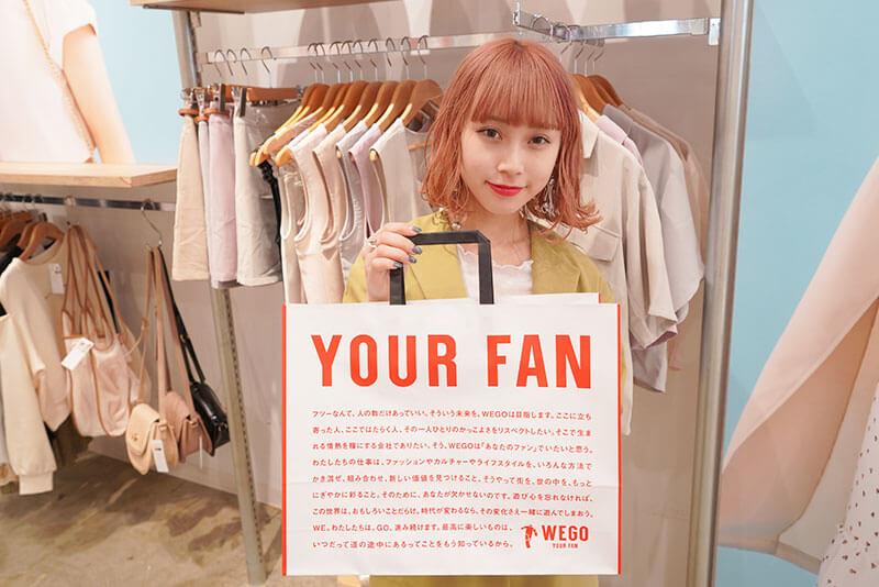 女性店員さんがショッピングバックを持っている画像