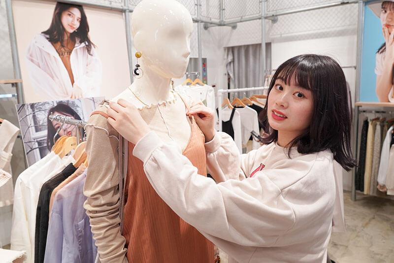 女性店員さんがマネキンの服を直している画像