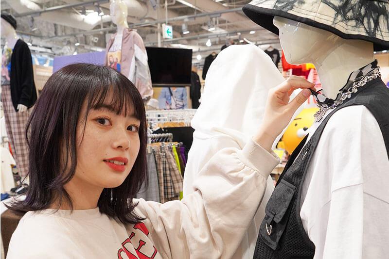 マネキンの服を直している女性店員さんの画像