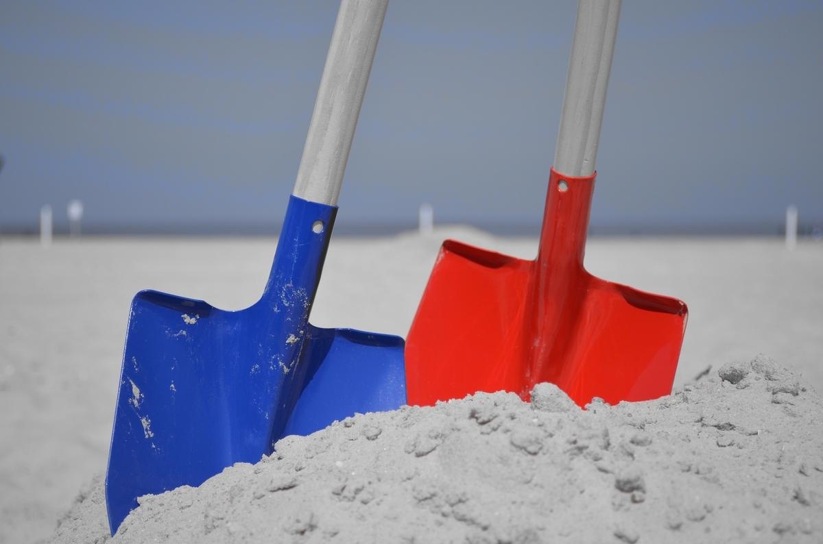 2つのスコップが砂浜に刺さっている。