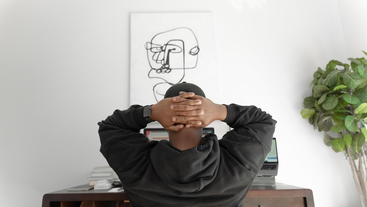 手を頭の後ろで組んでいる男性