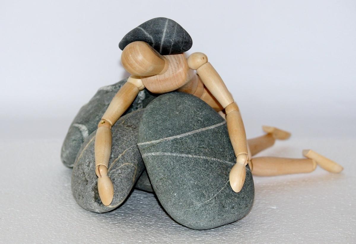 人形型のおもちゃの上に石が乗っかっている