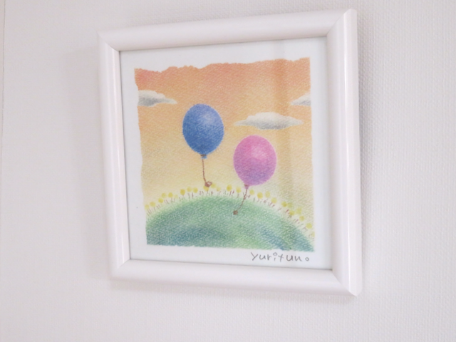 夕焼けに風船が二つ浮かんでるパステル画