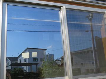 空が写り込んだ窓の画像
