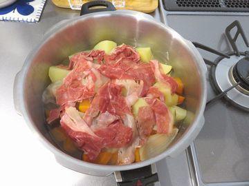 鍋に入った野菜の上に広げた肉