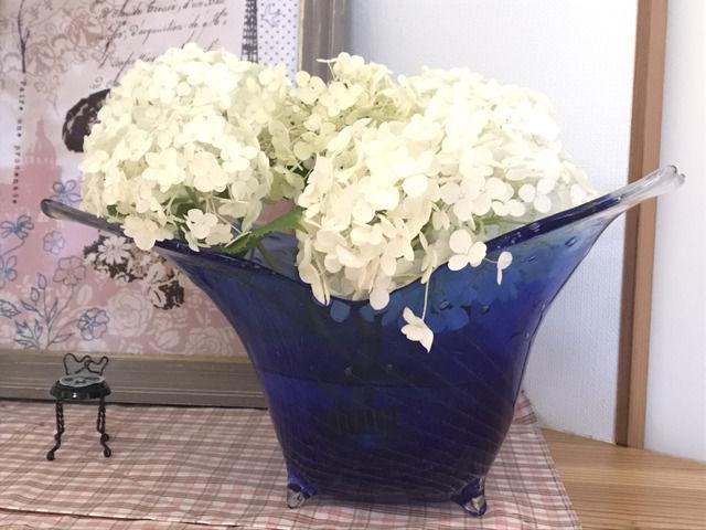 青いガラスの花器に生けた白いアナベルの花