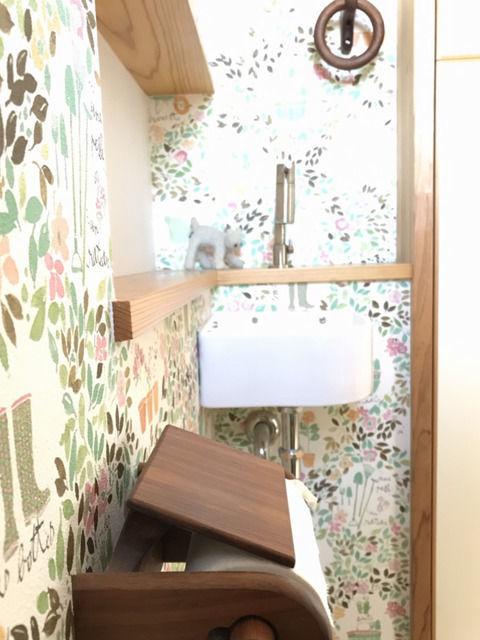 木製ペーパーホルダーとタオルリングのトイレ