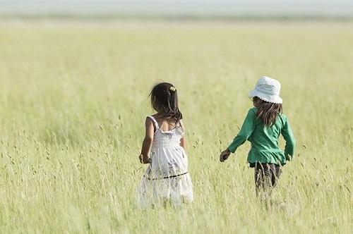 草原を歩く二人の子供