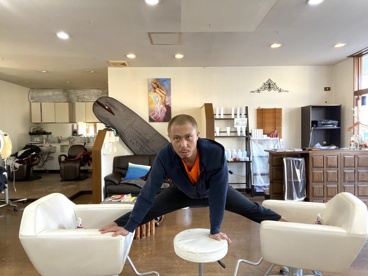 人が2つの椅子に足を片足づつ乗せ、1つの動く補助椅子使って開脚する