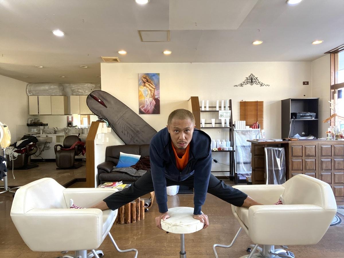 人が2つの椅子に足を片足づつ乗せ、1つの動く補助椅子を使い開脚する