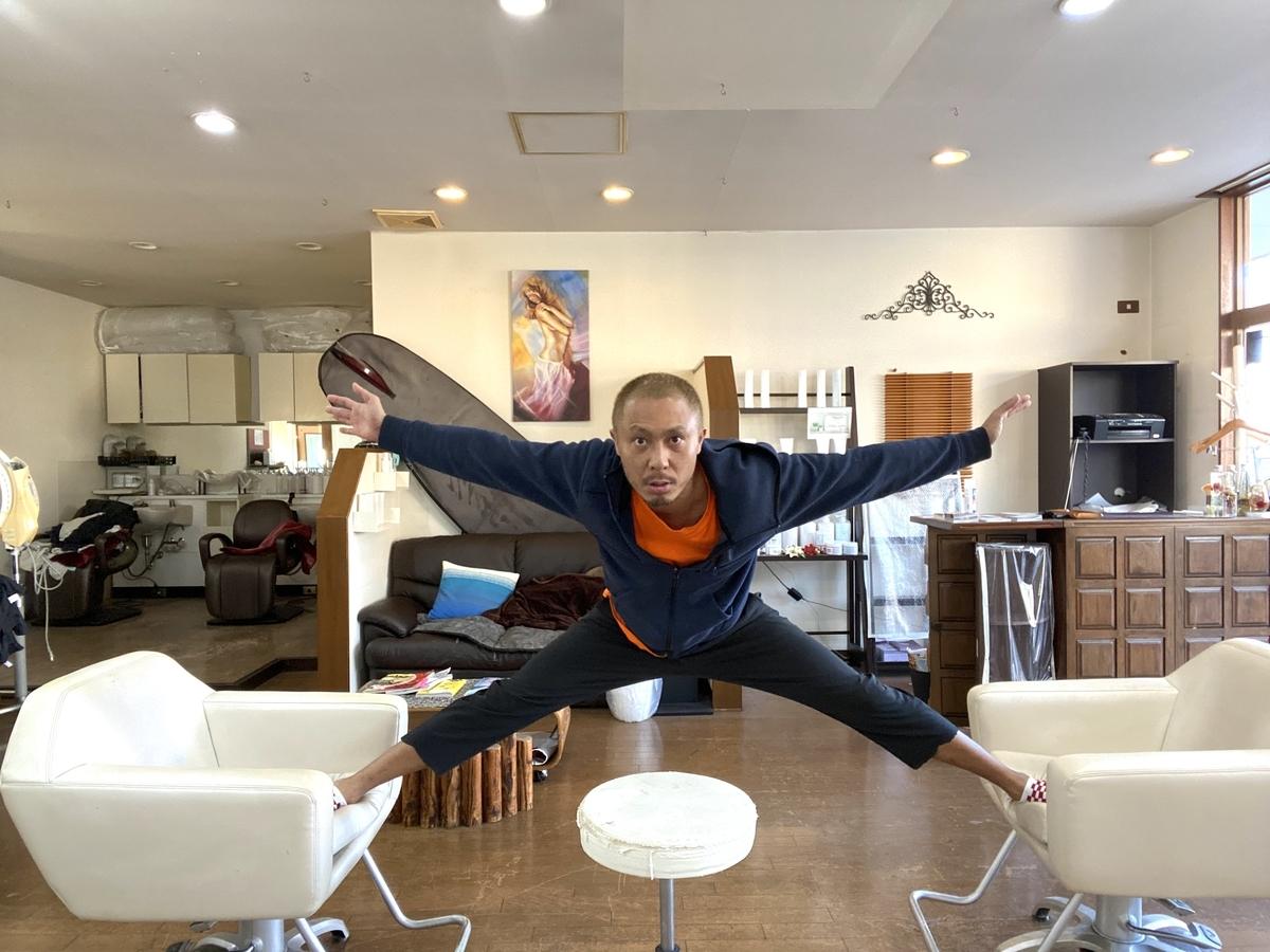 椅子2つと動く椅子1つ(補助椅子)を使って人が開脚し両手を腕から床と平行に持ち上げてる