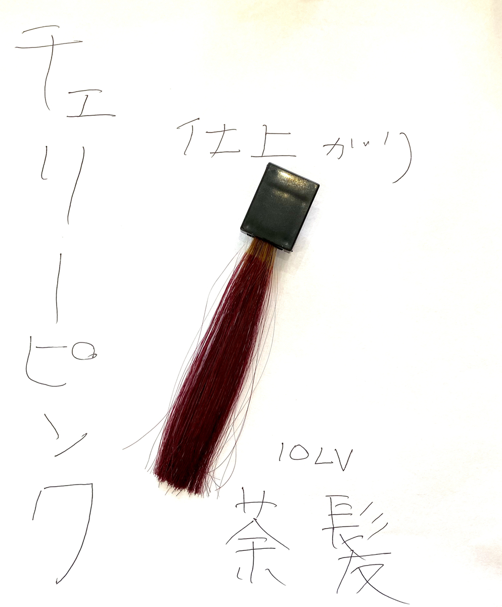 チェリーピンクで染めた後の茶髪の毛束