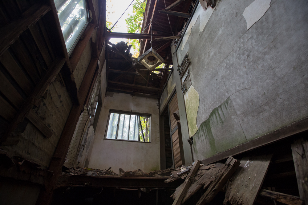 家庭用の照明器具がぶら下がる崩壊した小部屋
