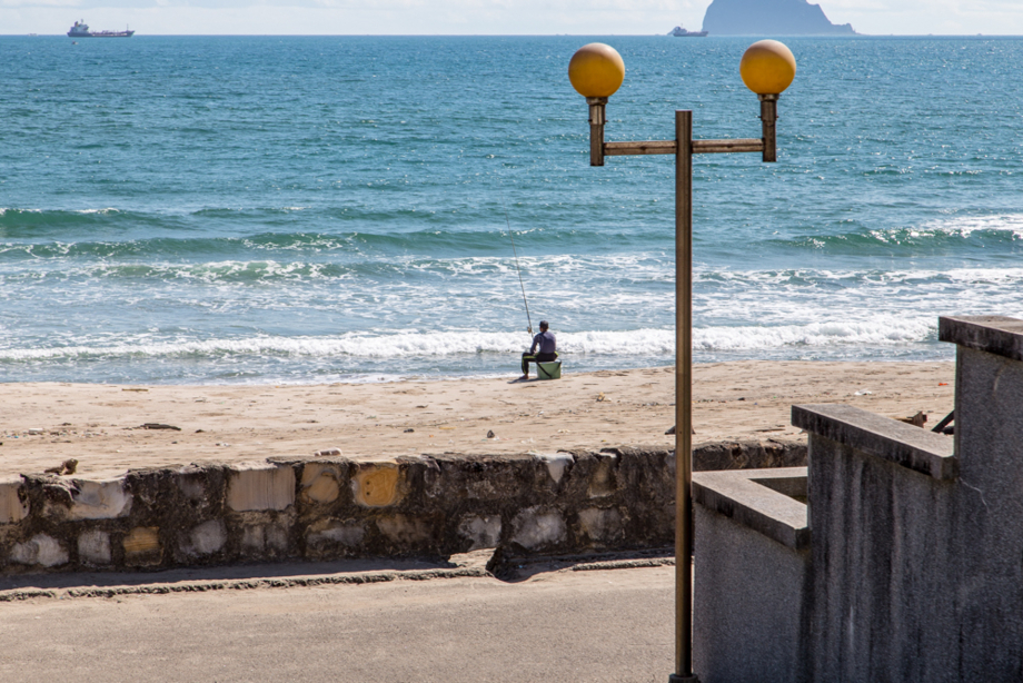 海沿いで釣りをする住人