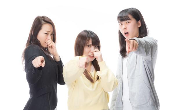 指をさす女性三人組