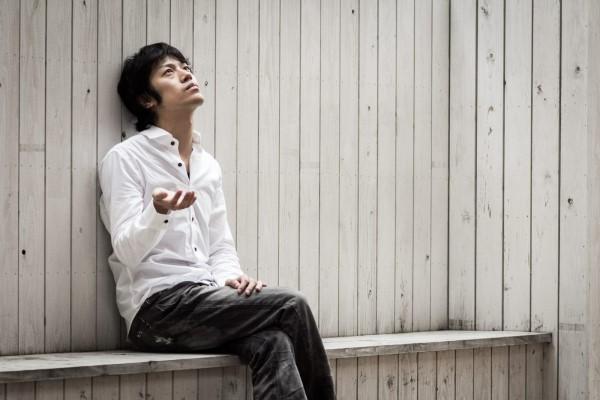 ベンチで空を見上げる男性