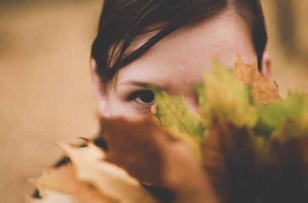 木の葉に隠れて覗く女性