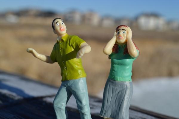 悩む女性と驚く男性の人形