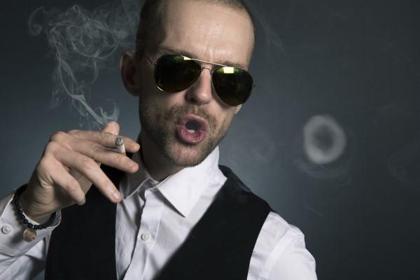 煙草を吸うサングラスの男