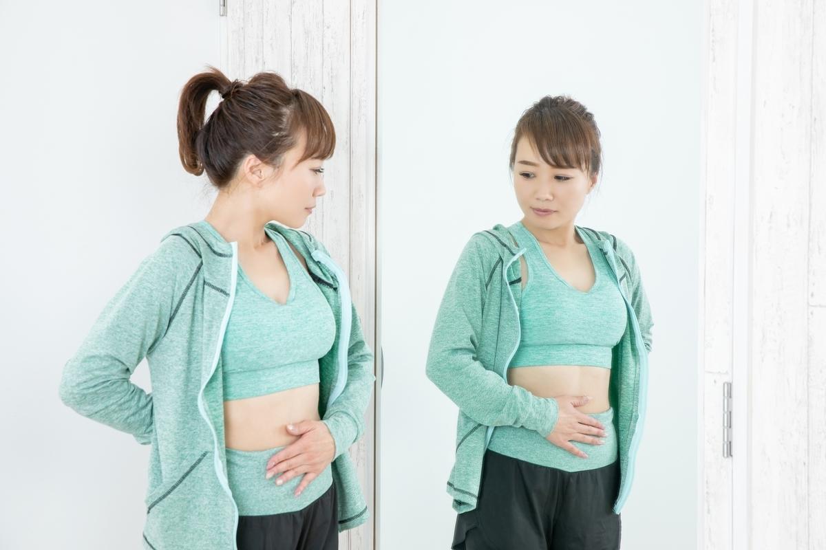鏡でお腹周りを見る女性