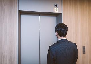 エレベーターの前で、待つ男性