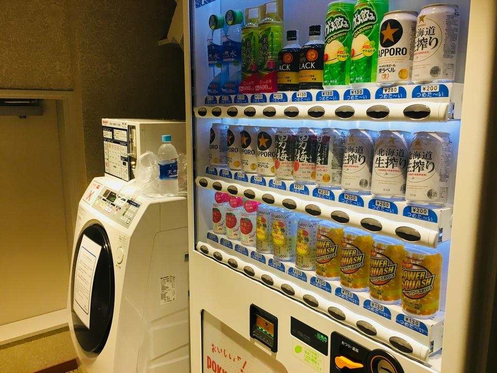 JR九州ブラッサム大分の洗剤自動投入の洗濯機と自販機の写真
