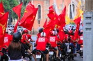ベトナムの旗を振るスクーター乗り達