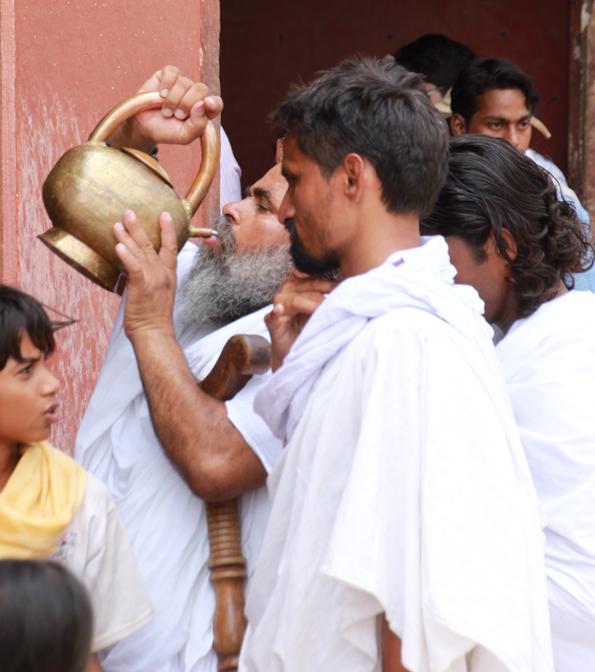 世界遺産「アーグラ城塞」でヤカンから飲み物を飲む男性