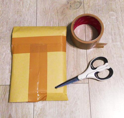本を入れた封筒をガムテープで留める