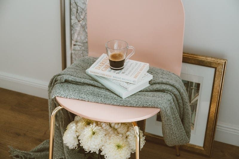 椅子に乗せられた本とコーヒとブランケット